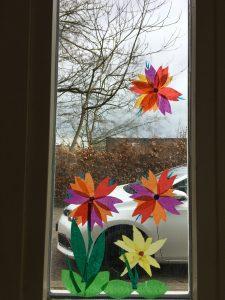 kleurrijke bloemen van papier op het raam